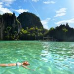 Woman resting on his back in the crystal clear water of island rock in the sun El Nido